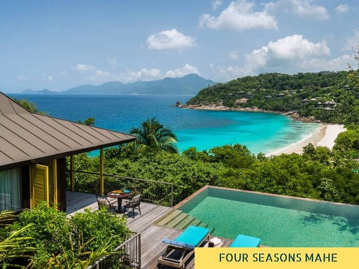 The swimming pool of Four Seasons resort on Mahe Island with the sea and the hills in the background