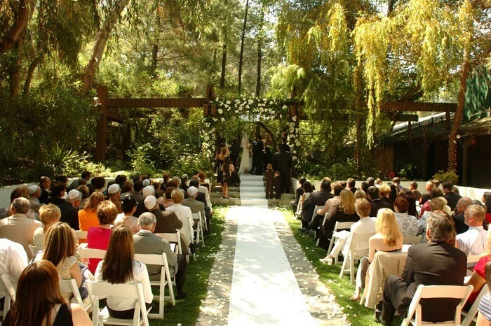 A couple exchanging vows at a covered area of Calamigos Ranch in Malibu