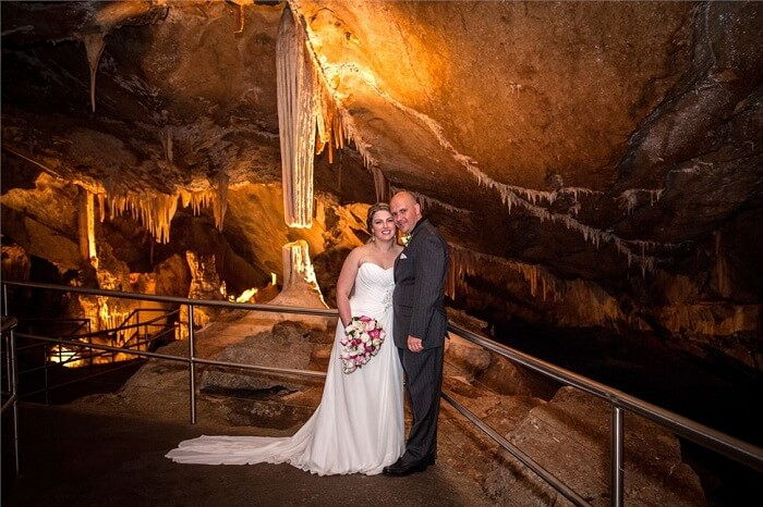 A couple poses at Jenolan Caves after the wedding ceremony