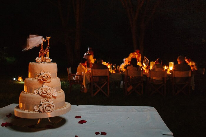 A shot of the guests dining and the wedding cake at Mara Bushtops in Kenya