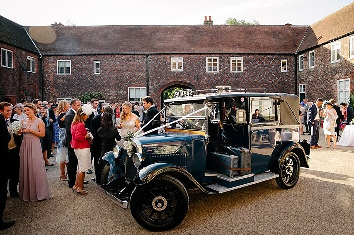 Bride and her best man at a wedding arrive in a car at Fulham Palace