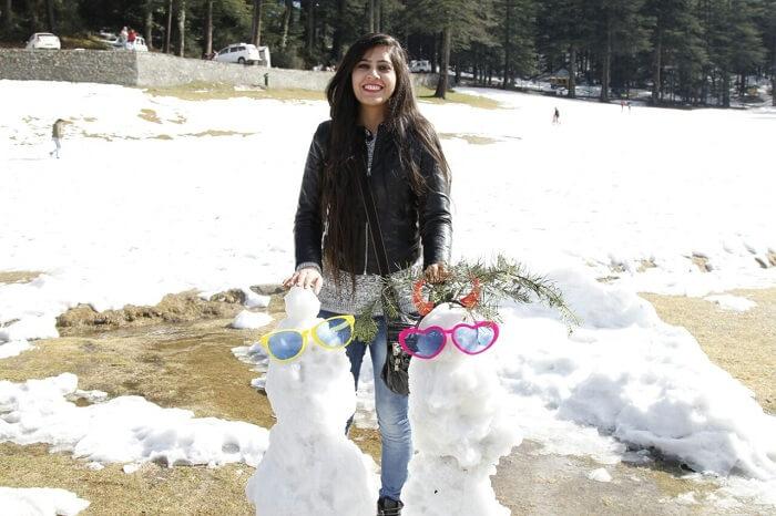 girl builds snow men in Dalhousie