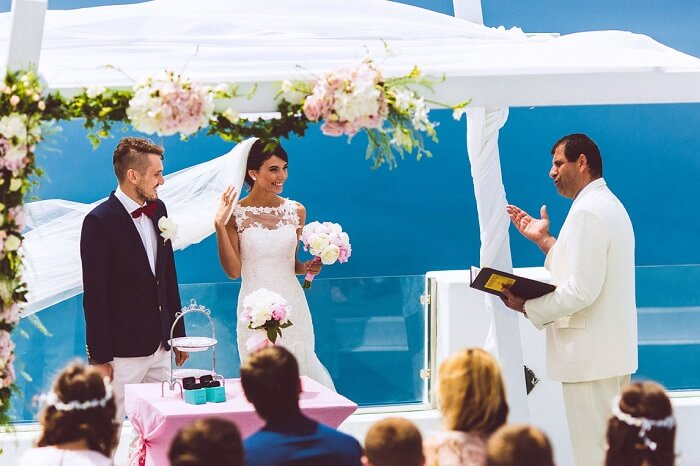 The priest makes a couple takes vows at La Maltese Estate of Santorini in Greece