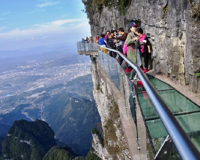 Women dizzying over the glass walkway at Tianmen Mountain Park in China