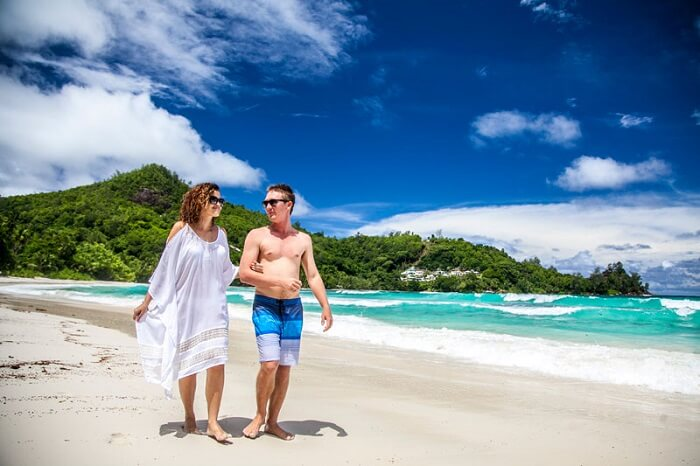 A couple enjoys a walk on the beach at Valmer Resort