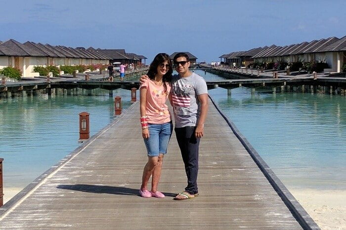 couple pose near water villas