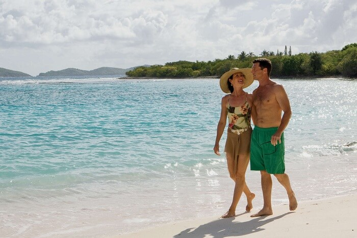 A couple takes a walk on the Pacquereau Bay beach near the Frenchman Cove resort in the US Virgin Islands