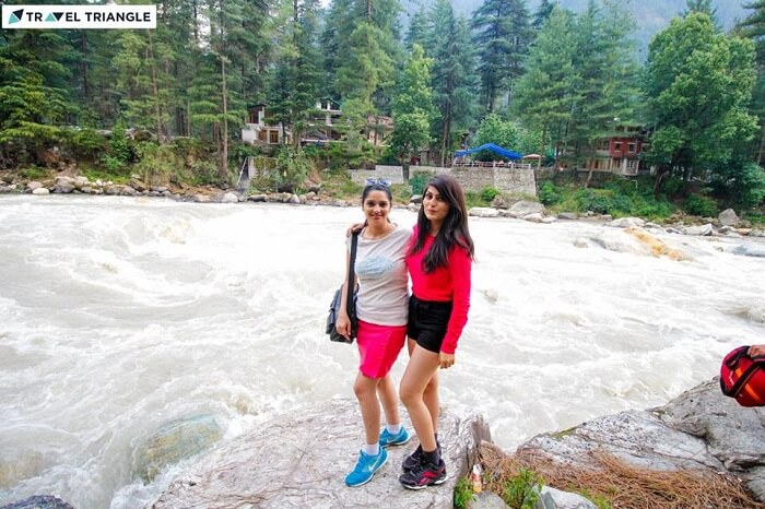 Young women travelers pose on the banks of a river flowing through Kasol