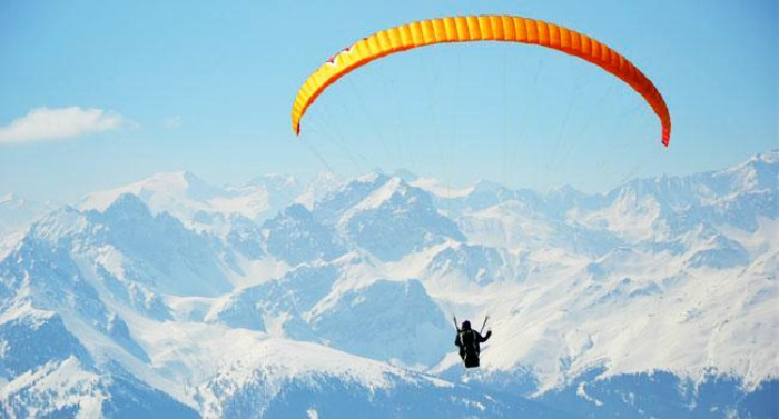 Paragliding over the snow-capped mountains of himalayas