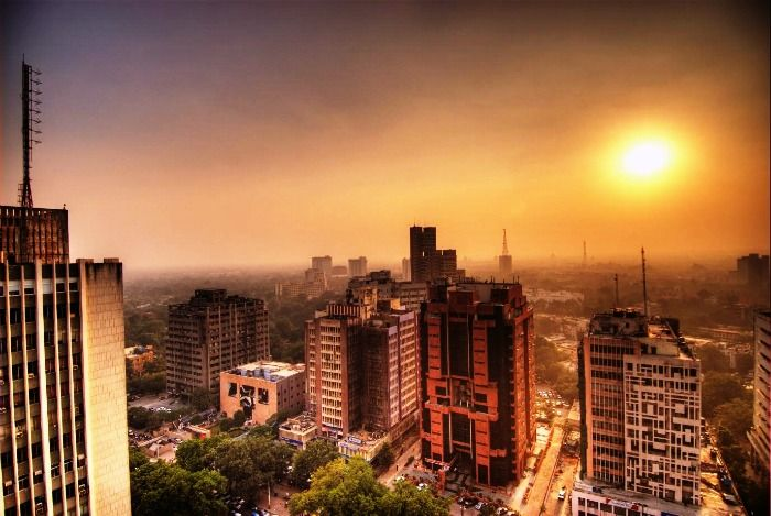 The tall concrete buildings of New Delhi during sunset