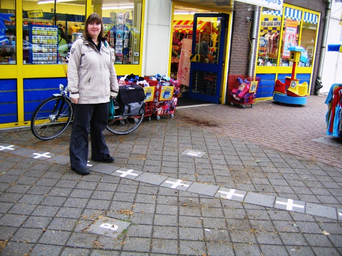 A woman stands on the International Border of Netherlands & Belgium