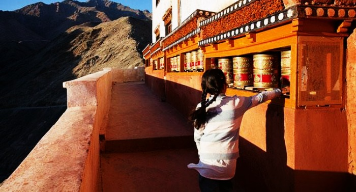 A little girl rotating the prayer wheel in Ladakh