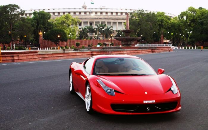 A red Ferrari on the wide roads of Delhi