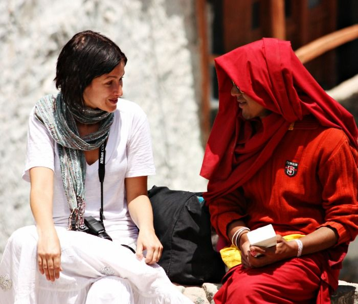 A tourist chatting with a monk at a monastery in Ladakh