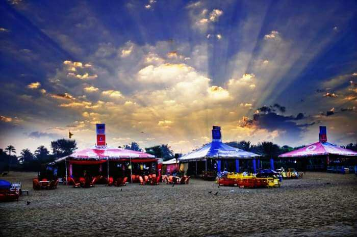 Dramatic skies and colorful shacks at Calangute beach in Goa