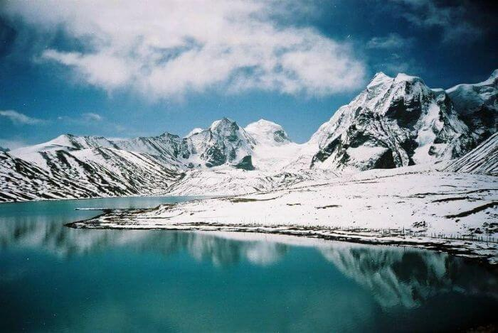 The surrounding snow clad mountains and the crystal clear icy water of Gurudongmar lake in Sikkim