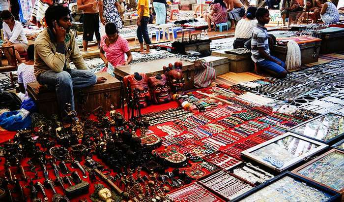 A shopkeeper selling junk jewellery and artefacts at Mapusa Market in Goa