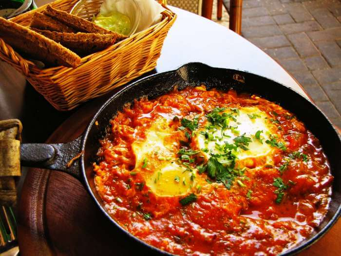 Shakshuka served with garlic bread and mint sauce.