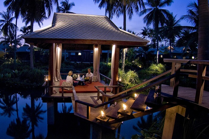 A couple having dinner by the swimming pool at the Anantara Mai Khao Phuket Villas