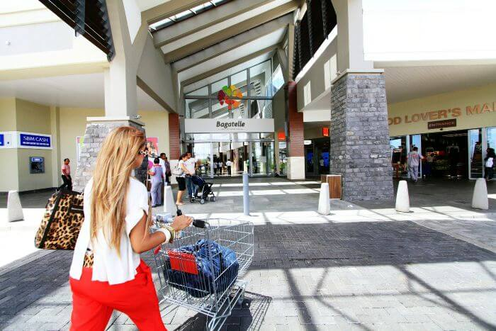 A lady walking with her shopping trolley inside Bagatelle Mall in Moka