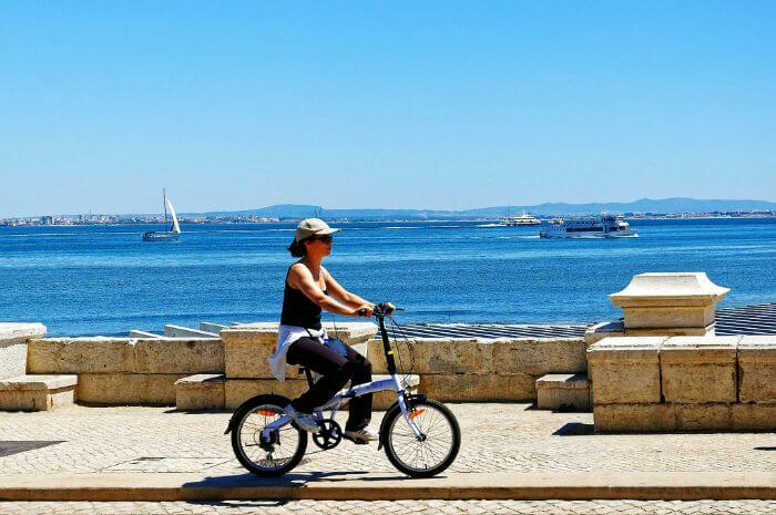 Woman riding a bicycle in Lisbon, Portugal