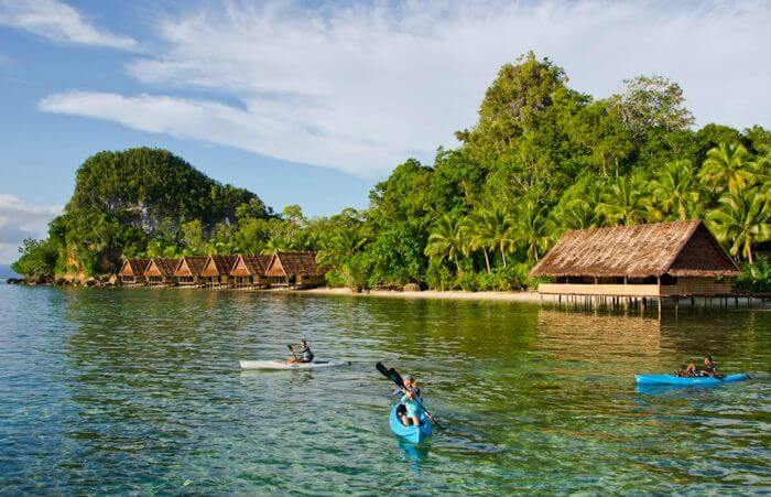 Guests enjoying kayaking in blue-green waters of Papua Paradise - an over water eco-resort