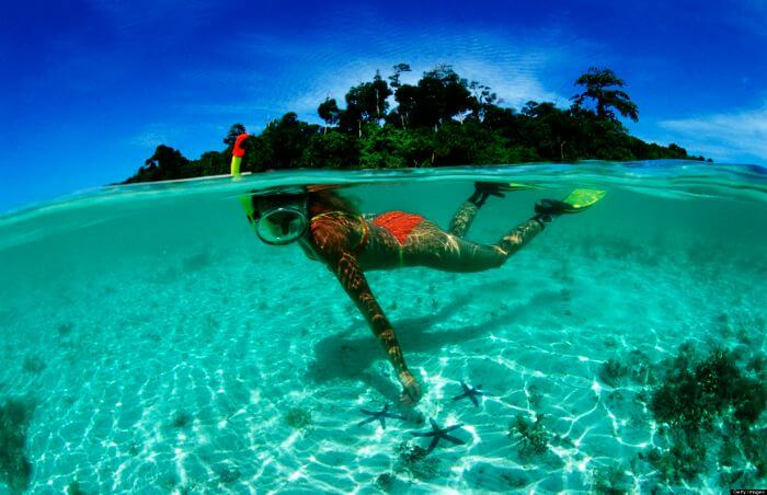 A young girl admiring the rich sea life while snorkeling at Pereybere beach