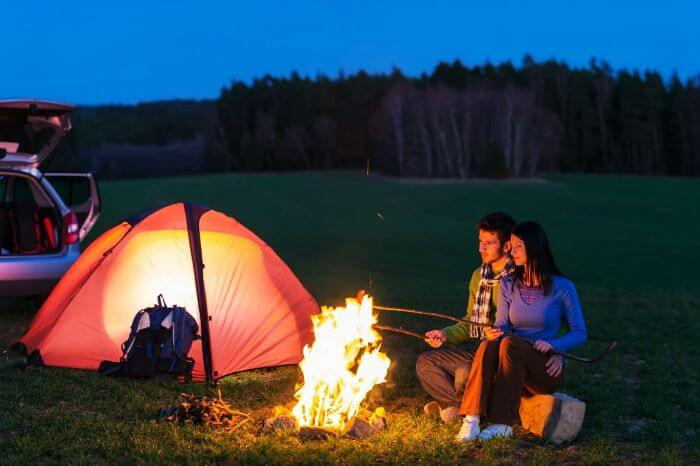 A couple at a campfire on their honeymoon.