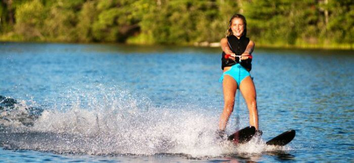 A girl enjoying water skiing on the blue waters of Bali