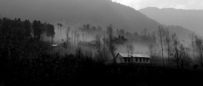 A house between the misty mountains and trees