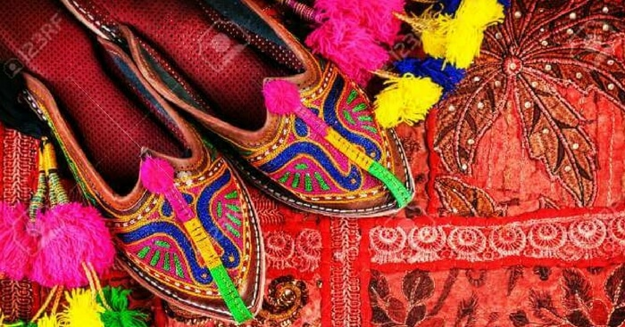 Traditional footwear on display with a colourful background in Jaipur