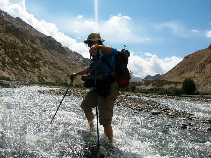 A trekker crosses a river during the ripchar valley trek