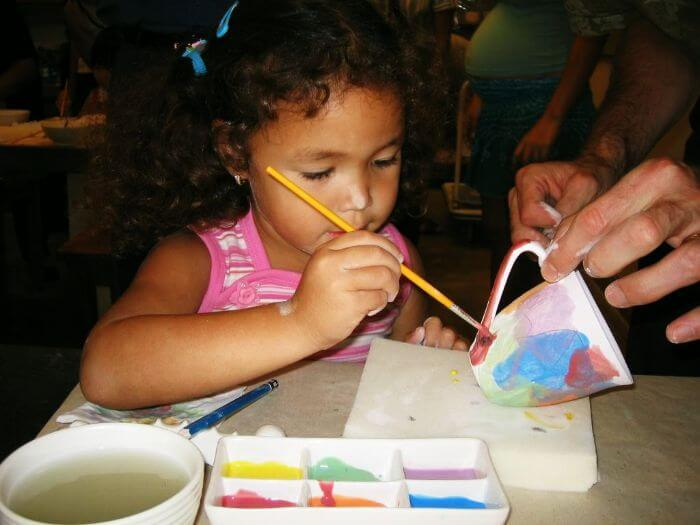 A girl trying her hand at a paint-a-pot workshop