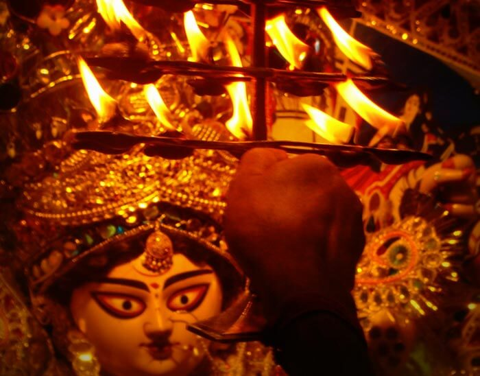 A man offering aarti to maa during Kolkata Durga Puja celebrations