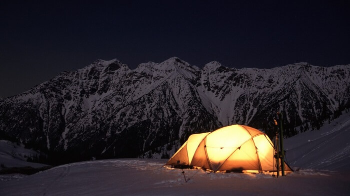 Camping in the snow with the mountains in the background