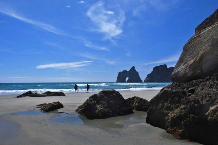 Travelers at Wharariki Beach on South Island