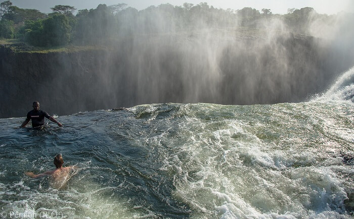 Tourists taking a bath at the Devil Pool at Victoria Falls