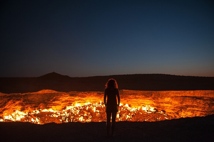 A woman stands at the edge of the door to hell in Turkmenistan
