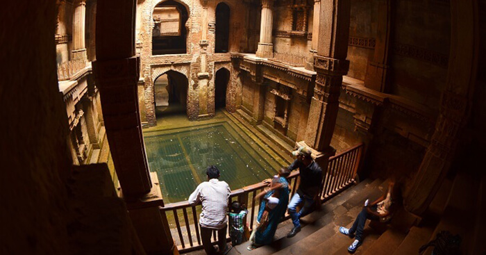 Visitors admire the beauty of architecture and carved walls of Adalaj Ki Vav near Ahmedabad