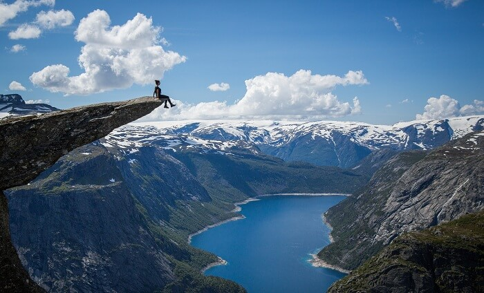 A girl sits at the cliff edge at Trolltunga