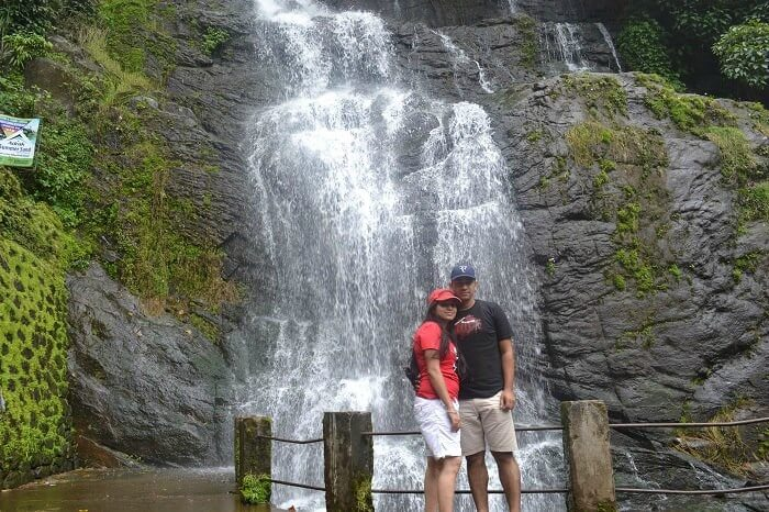 Rajeev and Neha posing in front of the waterfall enroute Alleppey to Thekkady