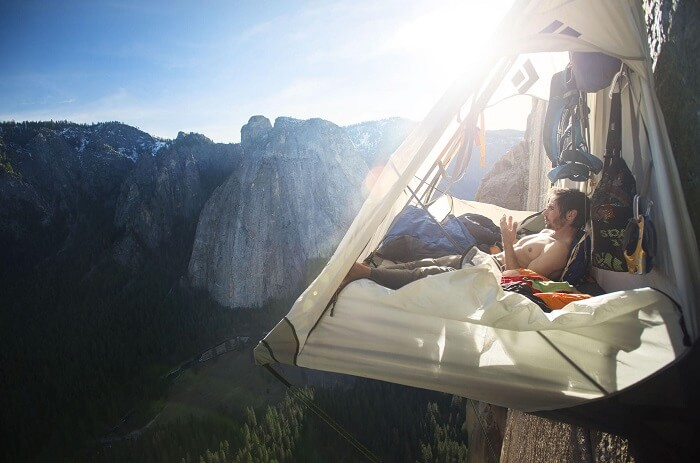 A man cliff camping on a mountain cliff