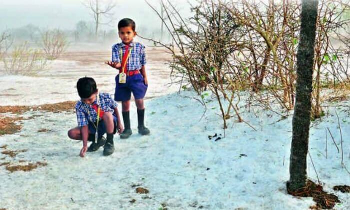 Two school kids playing with snow in Lambasingi