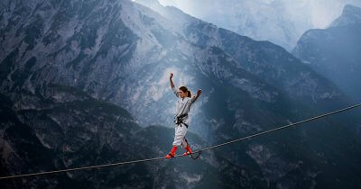 A woman highlining at theInternational Highline Meeting in Monte Piana