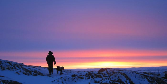 A man walks his dog in the snow in Iqaluit in evening while the sun still shines