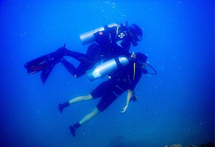 being helped by the professional while scuba diving in andaman