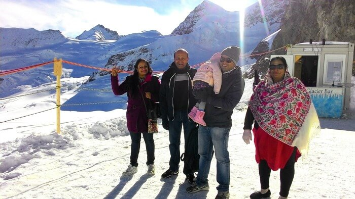 Enjoying a special family moment on top of the snow covered Alps