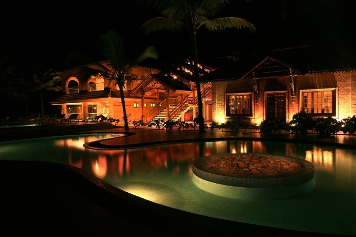 A view of the swimming pool at night at the Lakesong Resort in Kumarakom