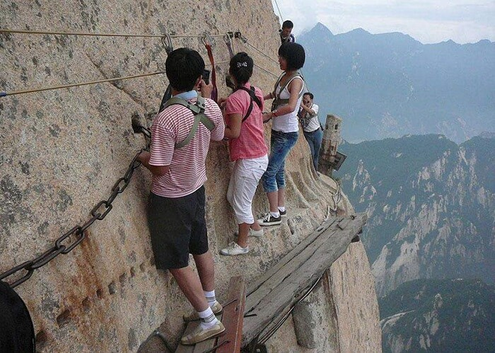People traversing the death-defying wooden planks of Mount Huashan trail