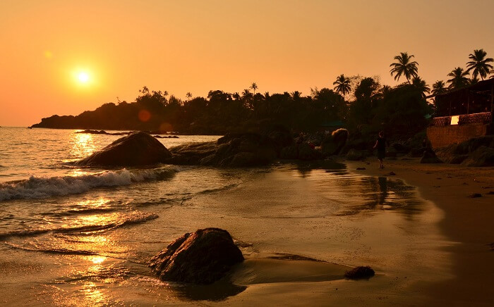 A woman walks on the Palolem Beach as the sun sets in Goa